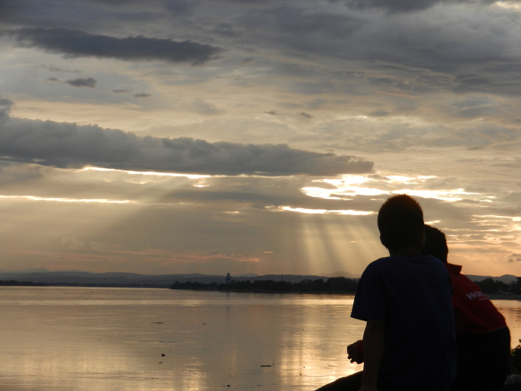 Residents in Vientiane look over the Mekong at sunset.