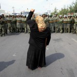 Uyghur woman facing a police cordon during protests in Xinjiang in 2009. Photo: REUTERS