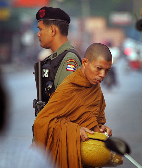 A Thai soldier guards a Buddhist monk as he collects alms. Photo courtesy of USA Today.